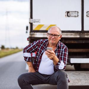 Trucker using TruckLogics mobile app for trucking dispatch.