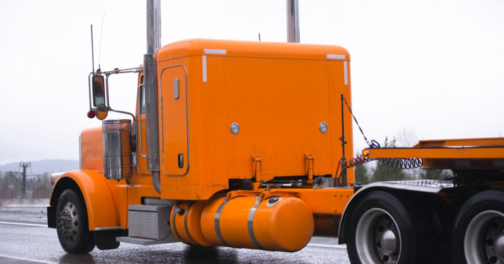 Orange truck in rain making money as an owner operator with trucking management software