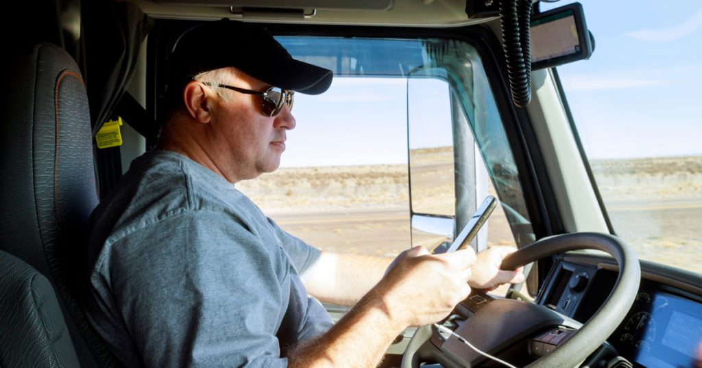 Trucker using TruckLogics trucking management system mobile app