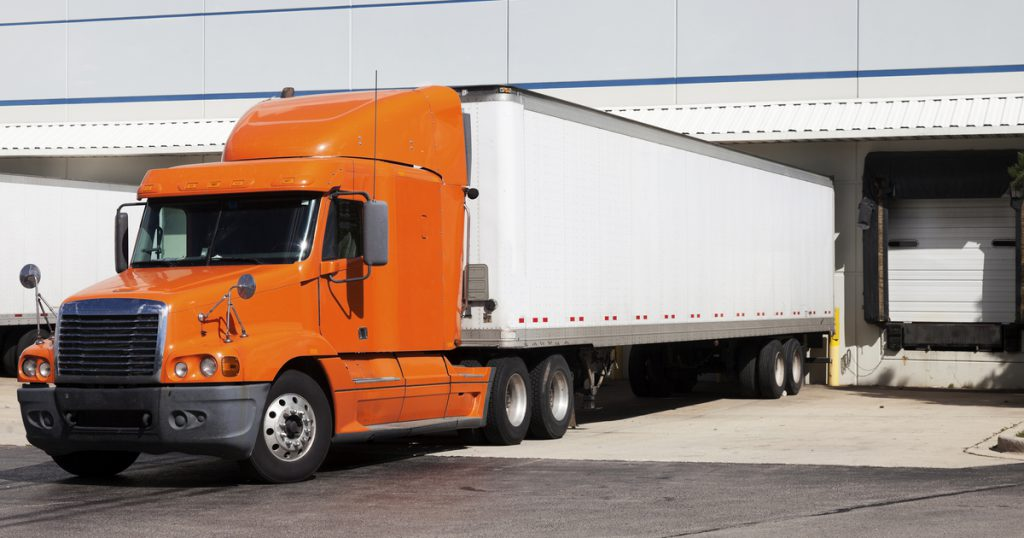 Orange truck parked in dock using TruckLogics TMS