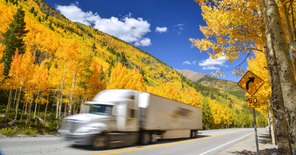 Company driver in fall using TruckLogics mobile app trucking management software for drivers