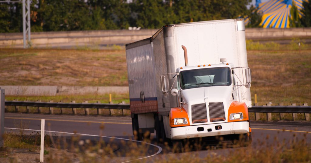 orange and white truck on interstate saving on owner operator expenses